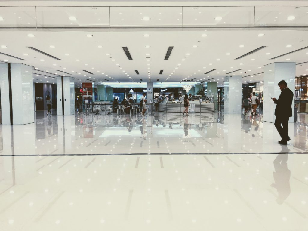 Hombre mirando el móvil en centro comercial
